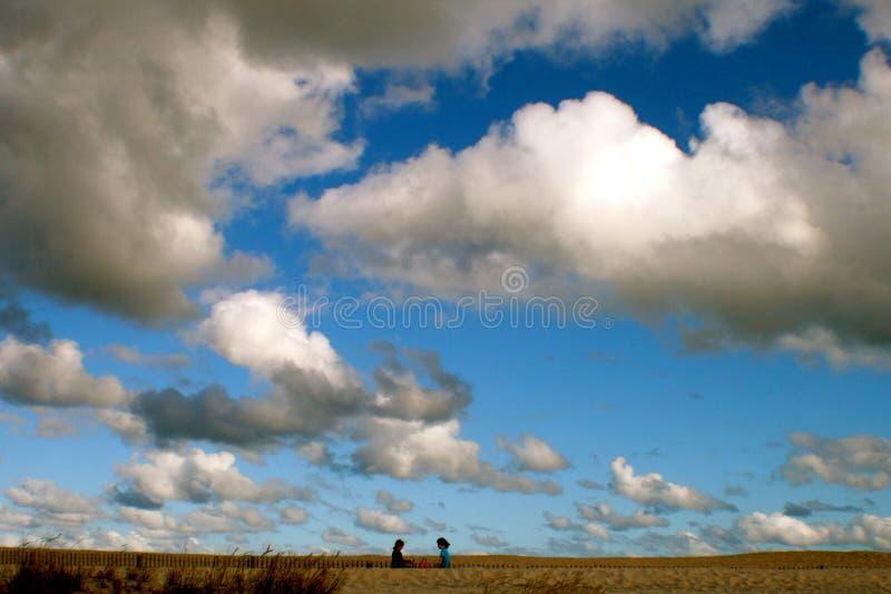 两个孩子谈话在与大天空的海滩在他们上 免版税库存图片