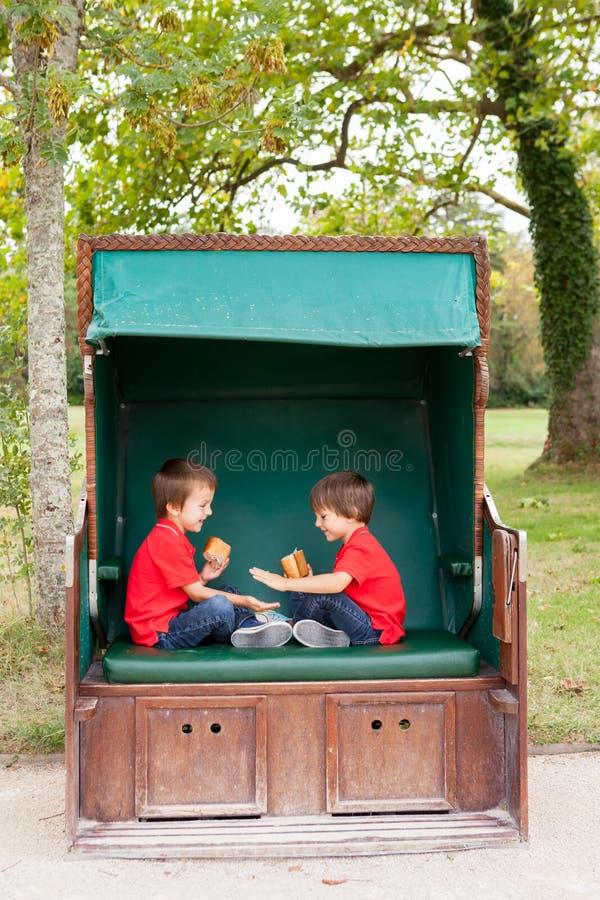 两个孩子,坐在一条被保护的长凳,演奏拍手ga 免版税库存图片