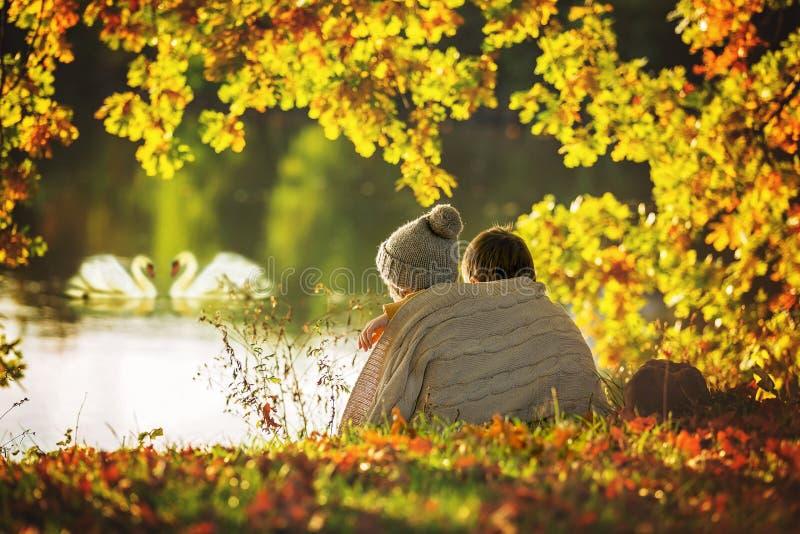 两个孩子,男孩,在湖边缘坐晴朗的秋天 免版税库存照片