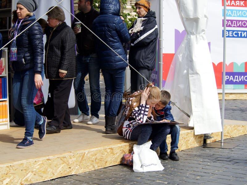 两个孩子-女孩和男孩看与兴趣的开放书 库存图片