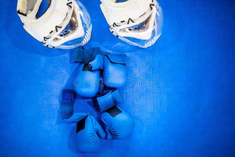两个对蓝色战斗的手套和两件白色盔甲与清楚的塑料穿孔的面具在蓝色地板上 空手道设备 免版税库存照片
