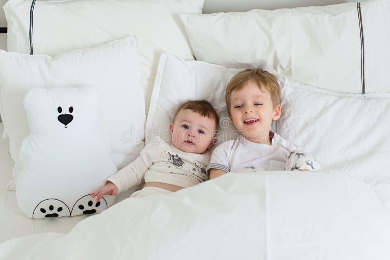 两个小俏丽的微笑的兄弟在床,滑稽的早晨上 图库摄影
