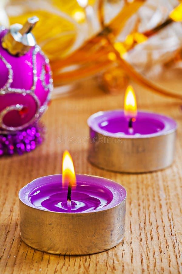 两个小发光的蜡烛和圣诞节球在木板 免版税库存图片