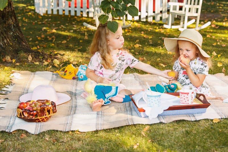 两个小女孩坐绿草 免版税图库摄影
