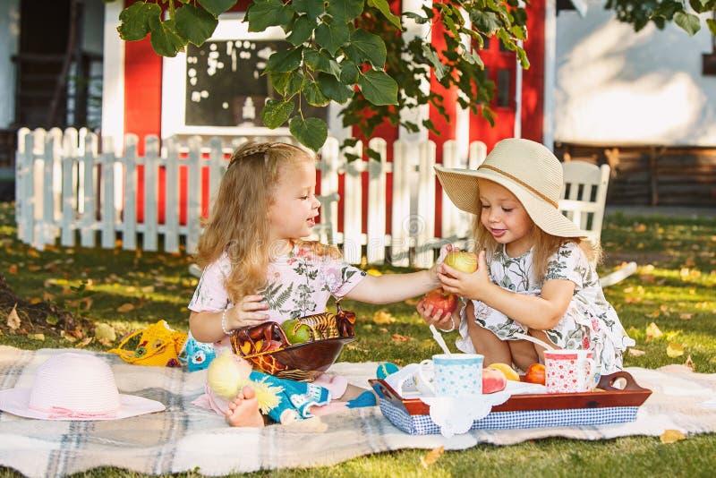 两个小女孩坐绿草 免版税库存照片