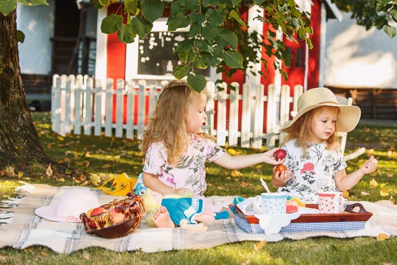 两个小女孩坐绿草 免版税库存图片