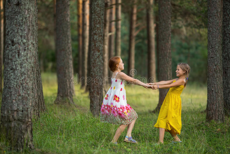 两个小女孩获得一起使用的乐趣在公园 库存图片