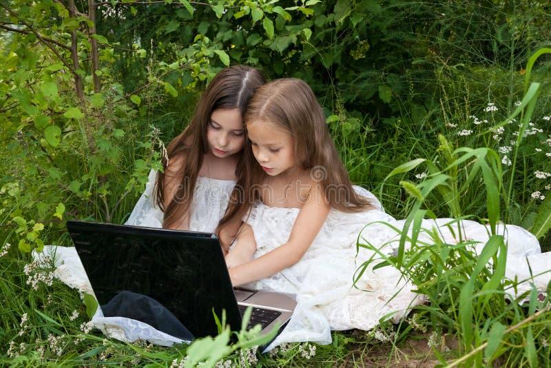 两个小女孩谈话在计算机后 库存图片