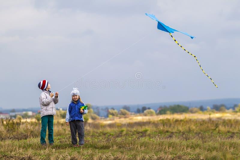 两个小孩使用外面与风筝的男孩和女孩 免版税库存照片