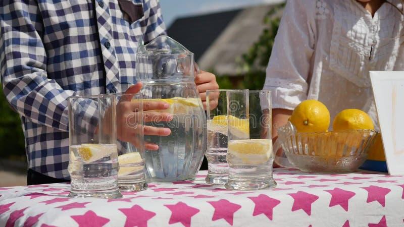 两个小孩卖柠檬水在一个自创柠檬水摊在与价格标志的一个晴天企业家的 库存照片