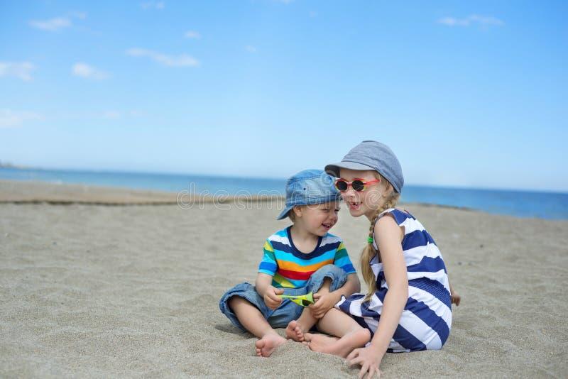 两个小孩子坐海滩 图库摄影