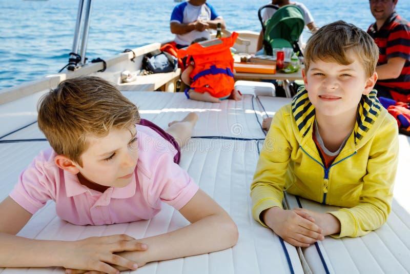 两个小孩男孩、父亲和享受帆船旅行的小孩女孩 在海洋或海的家庭度假在好日子 免版税库存图片