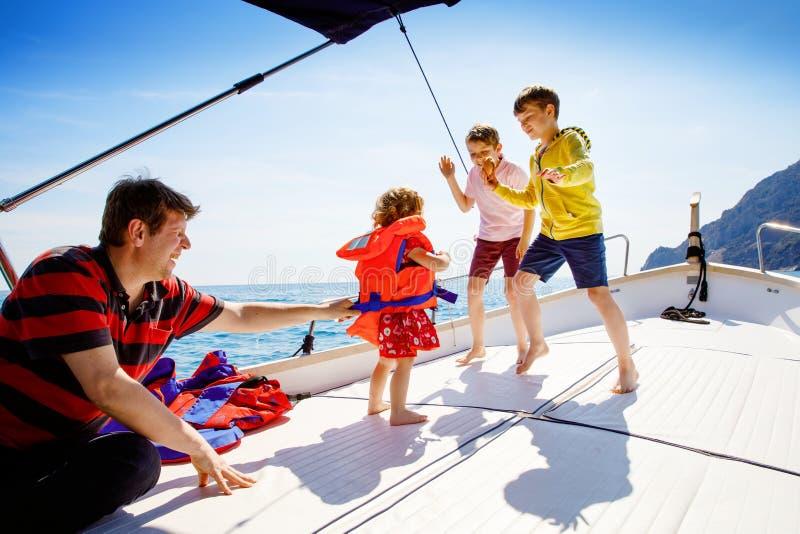 两个小孩男孩、父亲和享受帆船旅行的小孩女孩 在海洋或海的家庭度假在好日子 库存照片