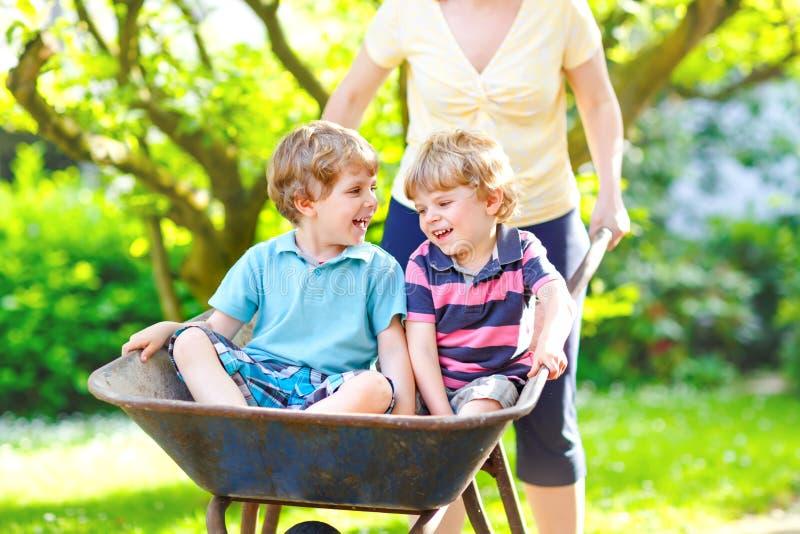 两个小孩男孩获得乐趣在推挤由母亲的独轮车在国内庭院里,在温暖的好日子 ?? 库存照片