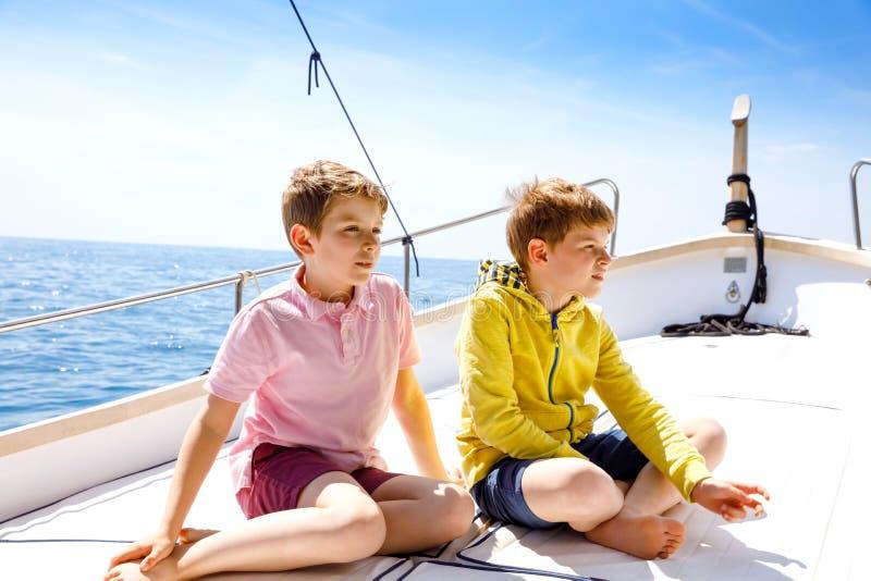 两个小孩男孩,享受帆船旅行的最好的朋友 在海洋或海的家庭度假在好日子 ?? 库存图片