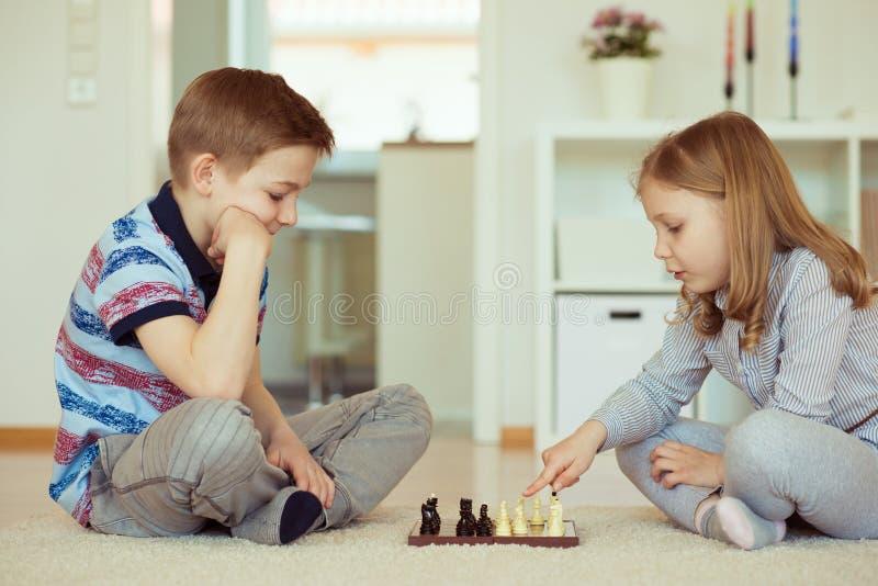 两个小孩画象集中了下棋 免版税库存照片