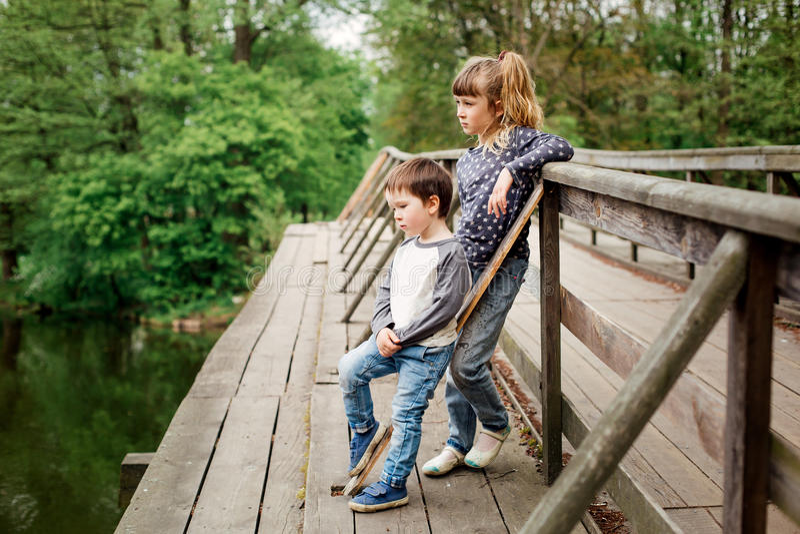 两个小孩,女孩和男孩,站立在桥梁 库存照片