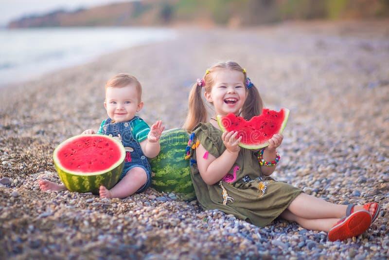 两个小孩,男孩女孩,吃在海滩的西瓜,夏令时享受接近海洋的好天气 免版税库存照片