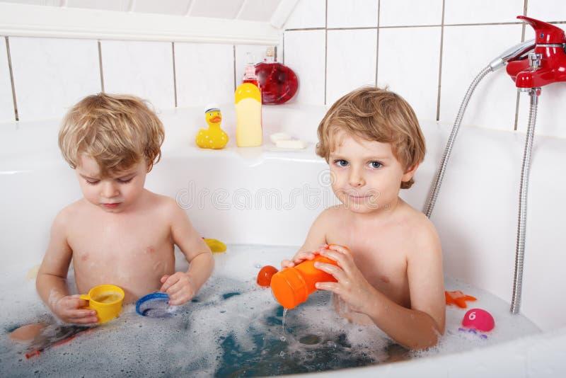 两个小孪生男孩获得乐趣用水通过洗浴在ba 图库摄影
