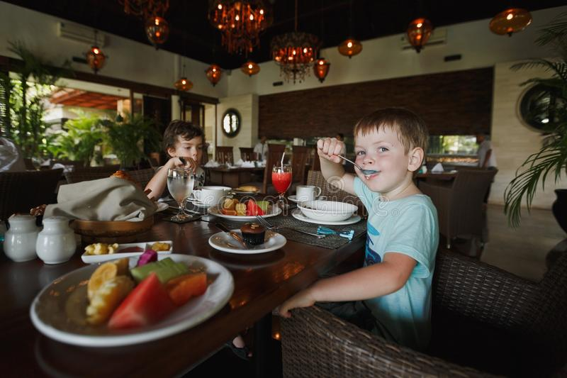 两个小男孩吃早餐在咖啡馆并且坐在饭桌上 在早餐桌上有有被切的异乎寻常的f的一块板材 免版税图库摄影