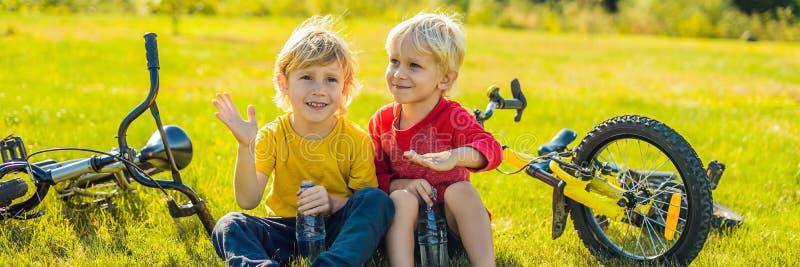 两个小男孩在乘坐自行车横幅以后喝水在公园,长的格式 库存照片