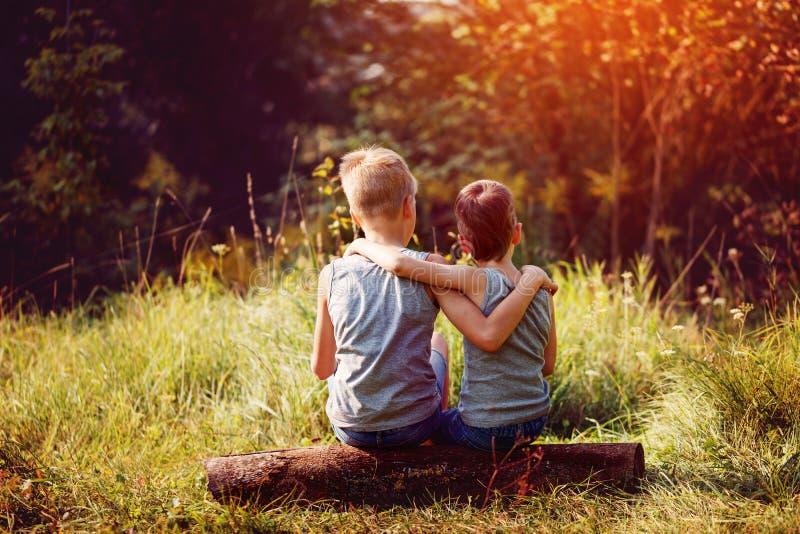 两个小男孩朋友在夏天晴天互相拥抱 兄弟爱 概念友谊 回到视图 库存照片