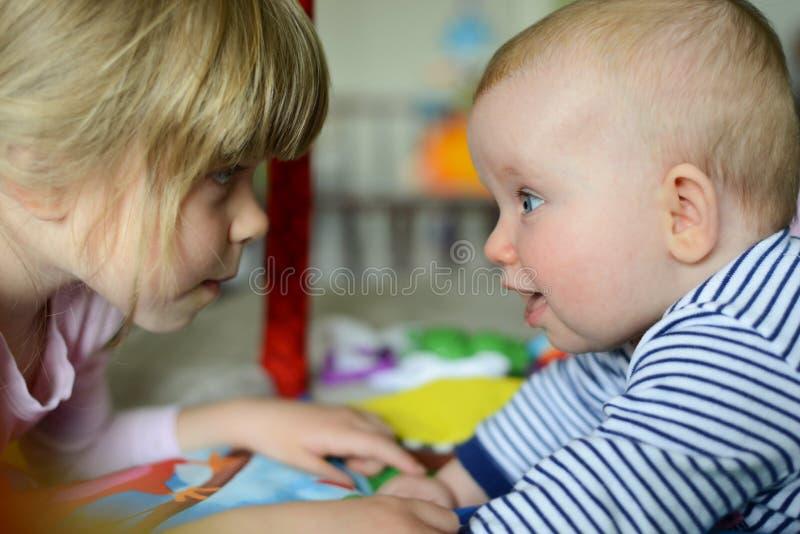 两个小的可爱的白种人姐妹看看彼此 他们是愉快和微笑 免版税库存图片