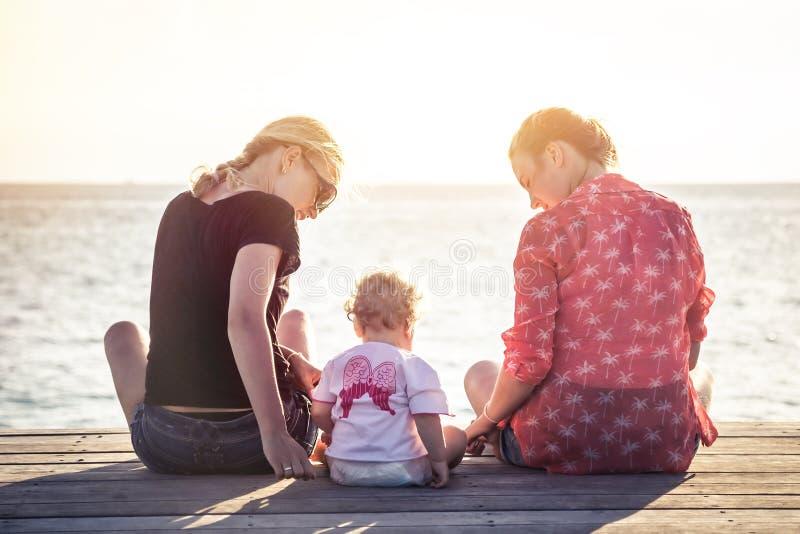两个少妇夫妇有孩子的坐木码头在与天际的日落期间在海在假期时 图库摄影