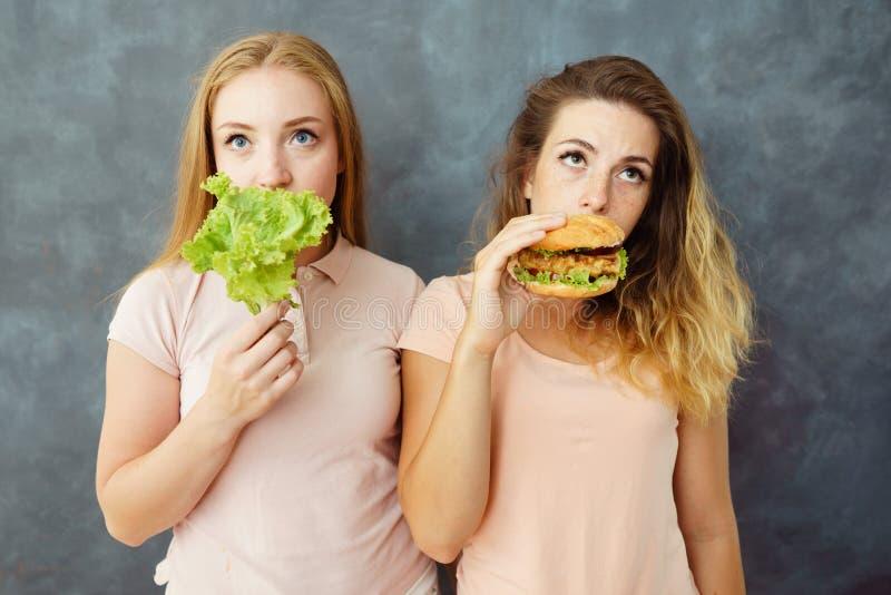 两个少妇用沙拉和汉堡包 库存图片