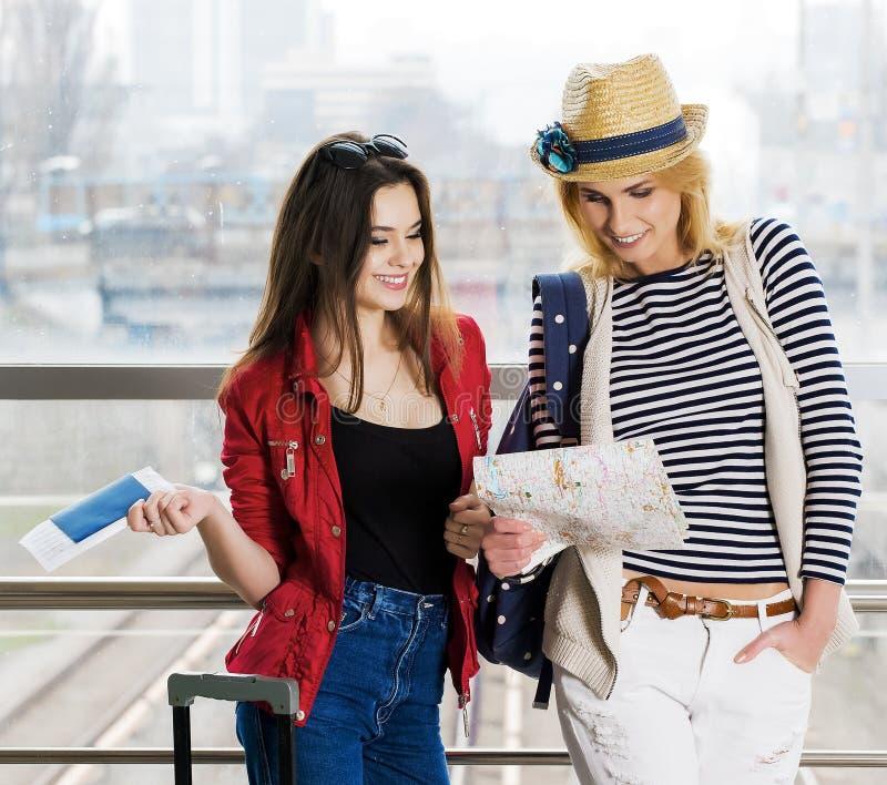 两个少妇站立带着手提箱在火车站或机场 看卡片和护照 免版税库存照片
