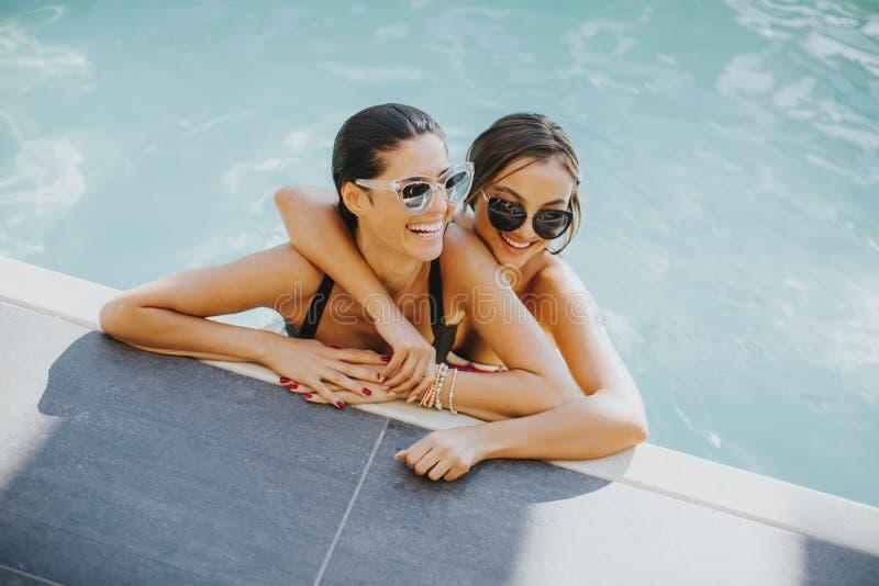 两个少妇获得乐趣在水池 免版税库存照片