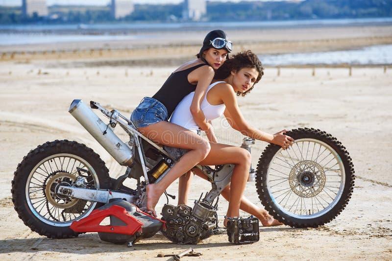 两个少妇获得使用在一辆被拆卸的摩托车的乐趣 图库摄影