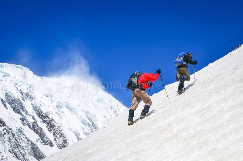 两个山背包徒步旅行者走在陡峭的小山的有下雪的峰顶背景,喜马拉雅山 库存图片