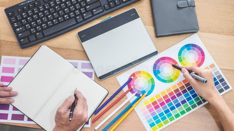 两个工作在颜色选择和画在图形输入板的同事创造性的图表设计师在工作场所,颜色样片 免版税图库摄影