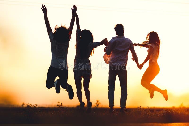 两个年轻人和两个女孩在一个夏日握他们的手并且跳在领域 回到视图 库存照片