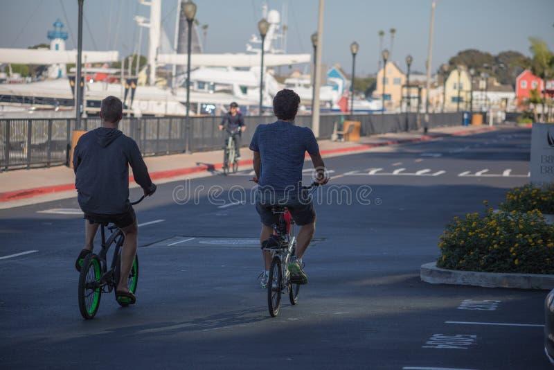 两个年轻人骑他们的沿小游艇船坞del木板走道的自行车  库存照片