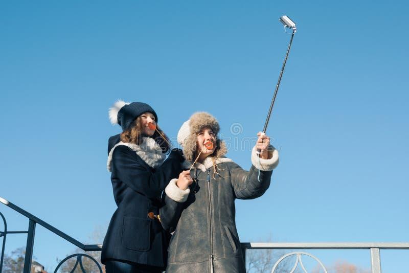 两个年轻十几岁的女孩有乐趣户外,愉快的微笑的女朋友在采取selfie的冬季衣服,正面人民和 免版税库存图片