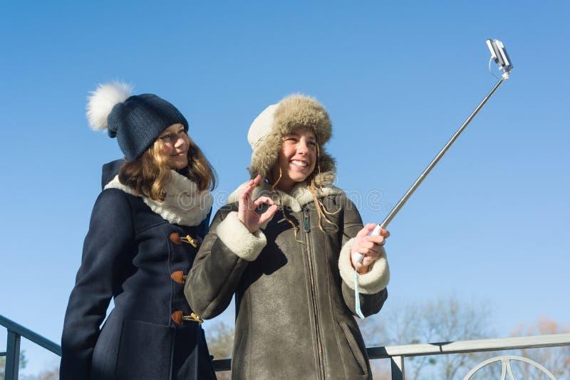 两个年轻十几岁的女孩获得乐趣户外,愉快的微笑的女朋友在冬天给采取selfie、正面人民和朋友穿衣 免版税图库摄影