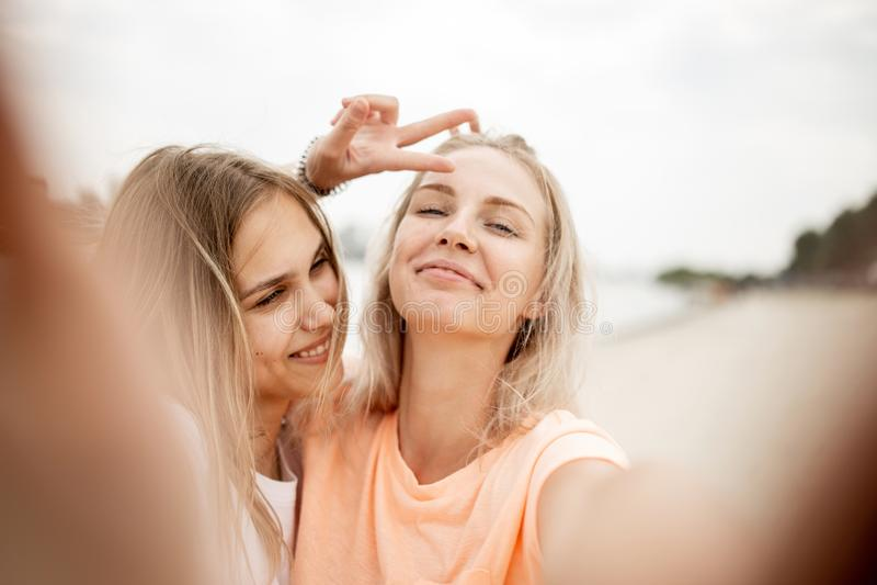 两个年轻可爱的白肤金发的女孩在一个温暖的大风天采取在海滩的一selfie 库存照片