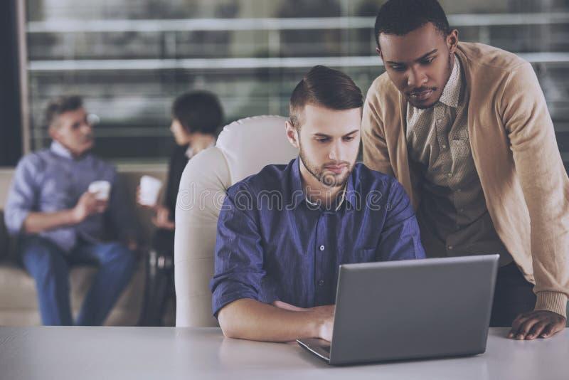 两个年轻商人谈论在膝上型计算机的一个新的项目在办公室 库存图片