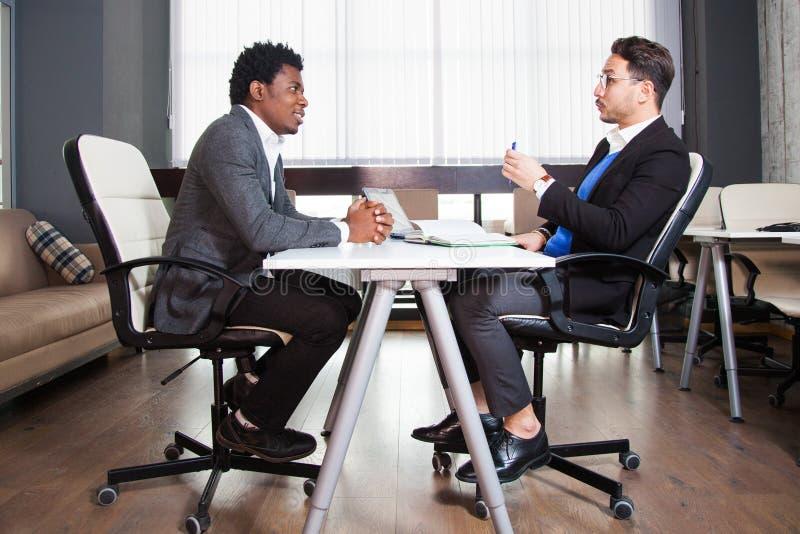 两个年轻商人,白色书桌,工作面试,配合 免版税库存图片