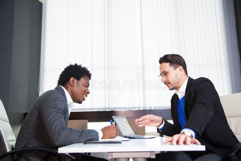 两个年轻商人,白色书桌,工作面试,配合 免版税库存照片