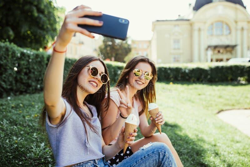 两个年轻女人朋友在夏天时采取selfie,当吃冰淇淋靠近河在日落 免版税图库摄影