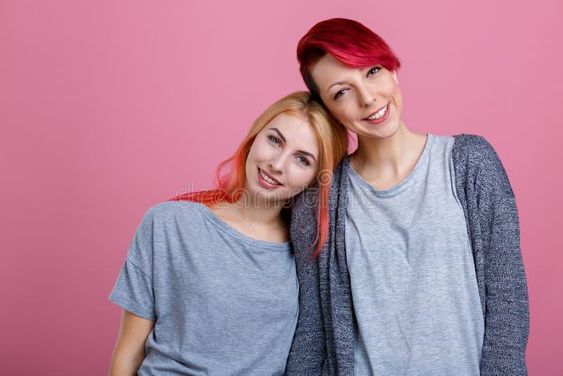 两个年轻女同性恋的女孩,接近彼此的立场,肉欲上拥抱和甜甜地微笑 在桃红色背景 免版税库存图片
