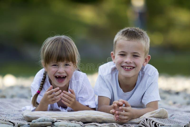 两个年轻愉快的逗人喜爱的白肤金发的孩子、男孩和女孩、兄弟和s 免版税库存照片