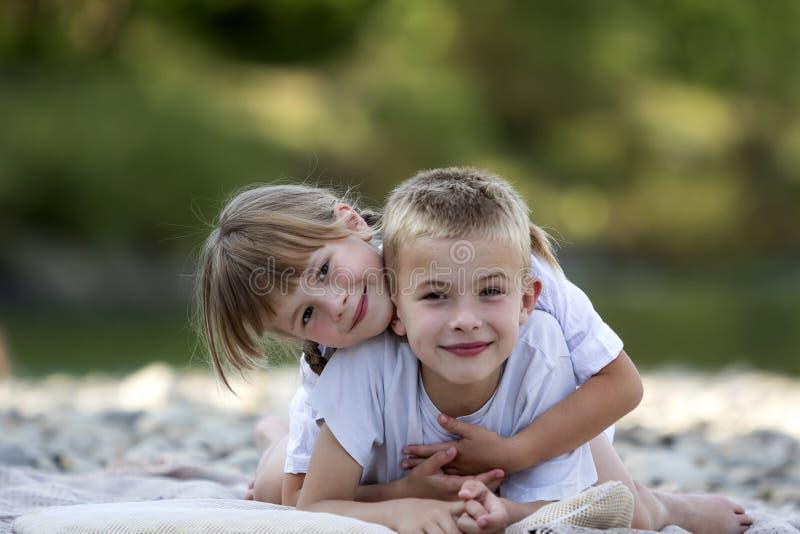 两个年轻愉快的逗人喜爱的白肤金发的微笑的孩子、男孩和女孩,汤 免版税库存图片