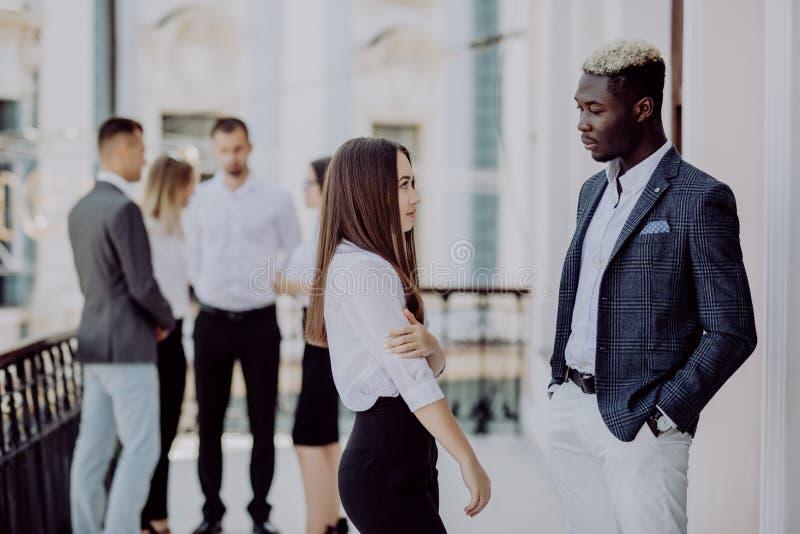 两个年轻混合的族种同事谈论在前面他们的企业队 免版税库存图片