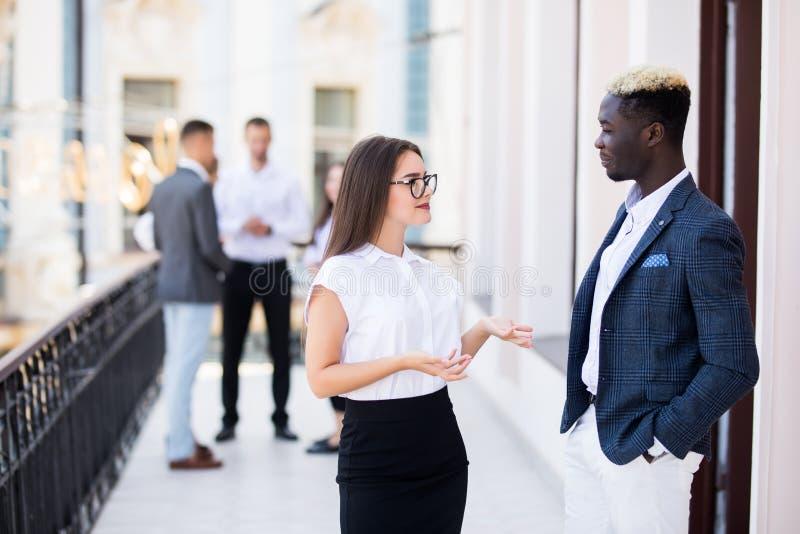 两个年轻混合的族种同事谈论在前面他们的企业队 库存照片