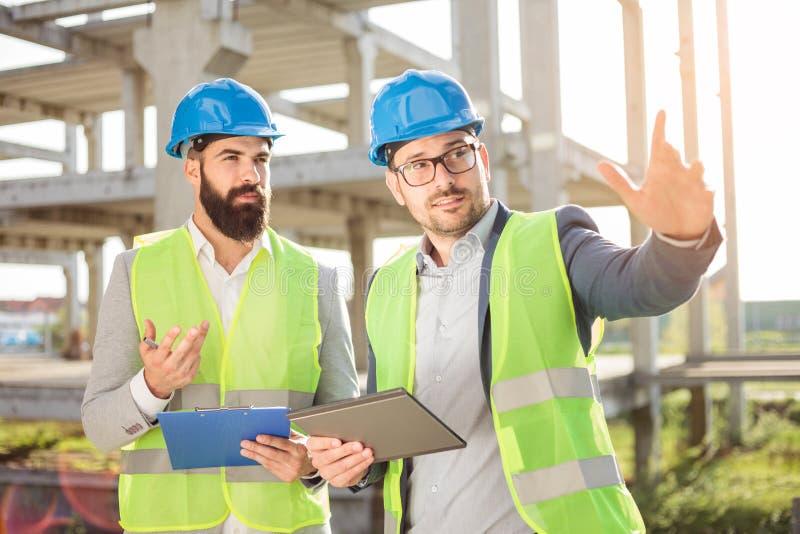 两个年轻男性建筑师或商务伙伴谈话在工地工作 库存照片
