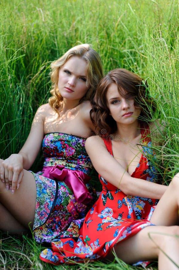两个年轻白肤金发的女孩和棕色毛发的妇女摆在夏天的明亮的礼服的在高草停放 免版税库存图片